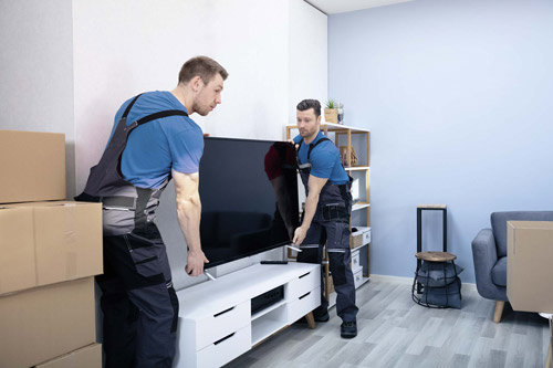 two men moving a tv