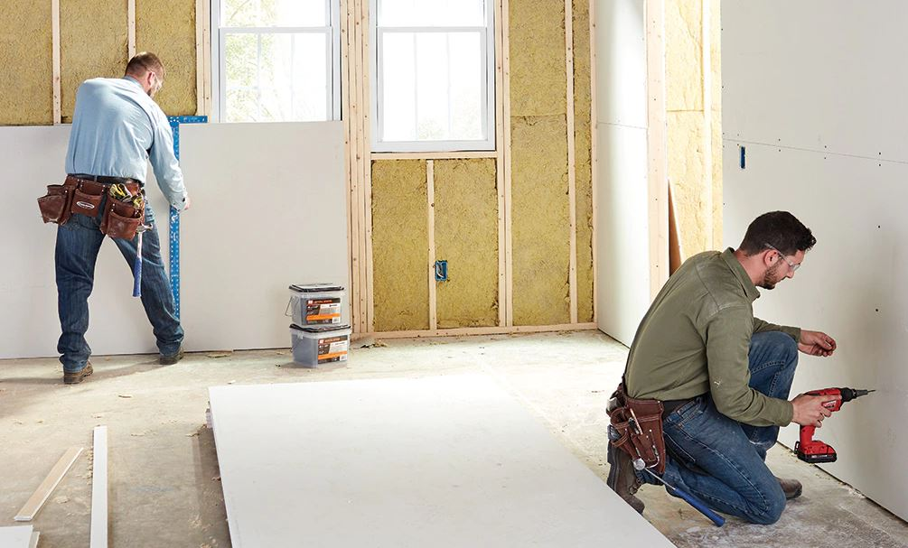 two drywallers measuring and installing drywall in des moines iowa